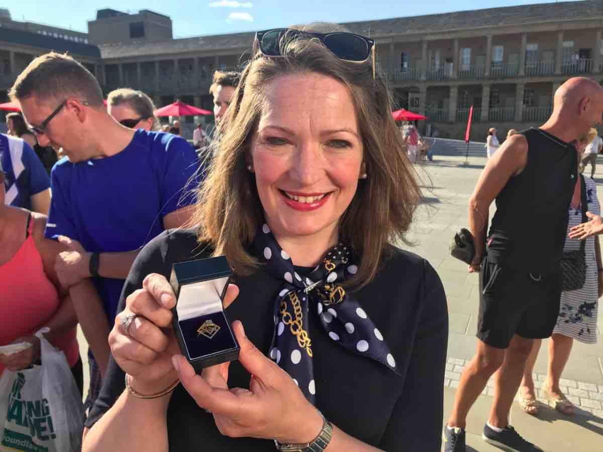 Susan Rumfitt holding gold brooch.