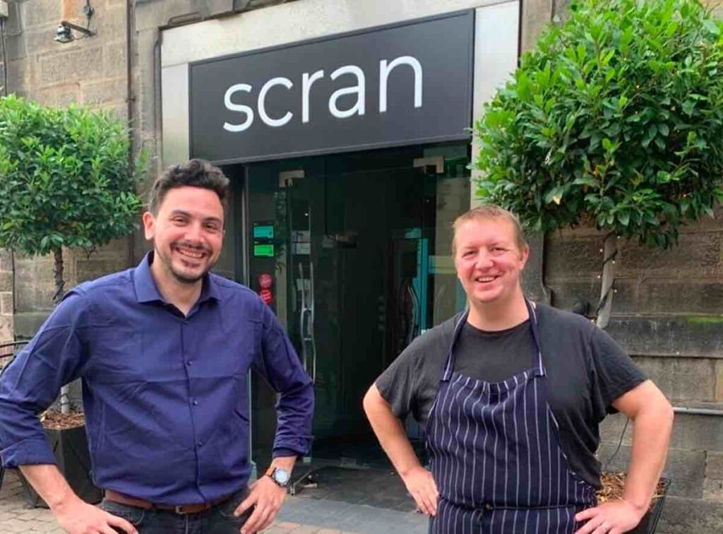 head chef and bar manager outside hotel