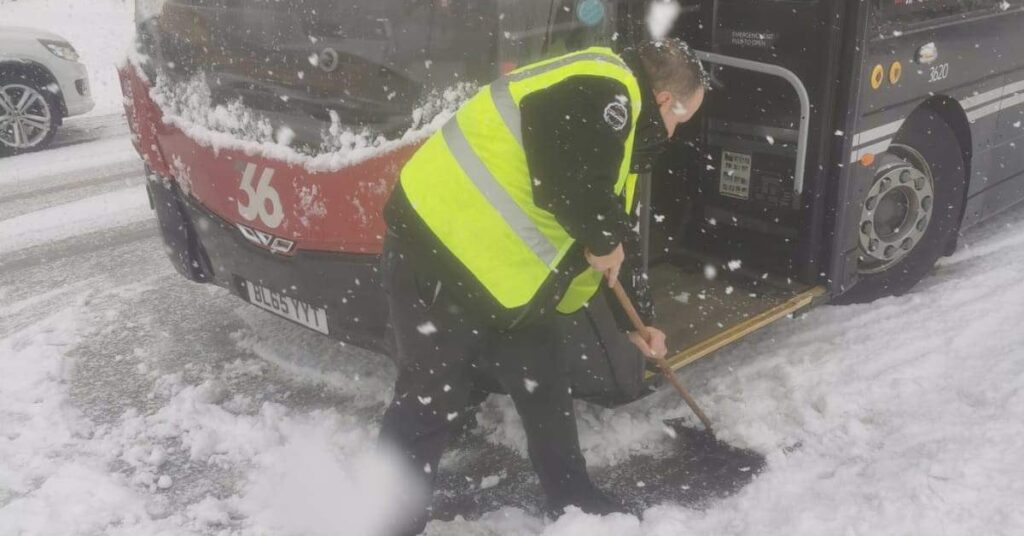 A member of Harrogate Bus Company staff clears the road